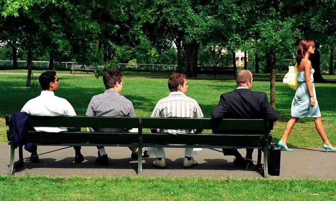 Four men on park bench watching young woman walking past